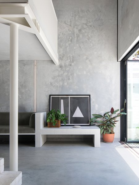 In defiance of its oversized neighbors, this sustainable 753-square-foot home in Perth, by architecture firm Whispering Smith, maximizes its small footprint through built-in furniture and textures of concrete, reclaimed brick, tile, and white metal. Devoid of walls and doors, the streamlined spaces flow into one another, and connect to the ample rear courtyard.