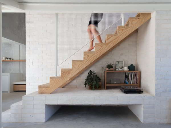 "Recycled bricks form a core wall and support the central staircase. A white metal railing is another layer of texture in the scheme. ""The project relied heavily on craft, detailing, and a raw material or 'wabi-sabi' spec to provide amenity and delight in the small footprint,"" say the architects."