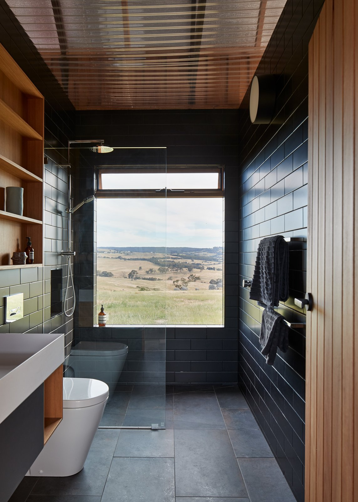 Bath Room, Ceramic Tile Wall, Vessel Sink, Full Shower, Wall Lighting, Ceramic Tile Floor, Corner Shower, and Open Shower The view is the focal point in a bathroom sheathed in charcoal tile and complemented by wood accents.    Photos from Simplicity Reigns at This Off-Grid Australian Retreat