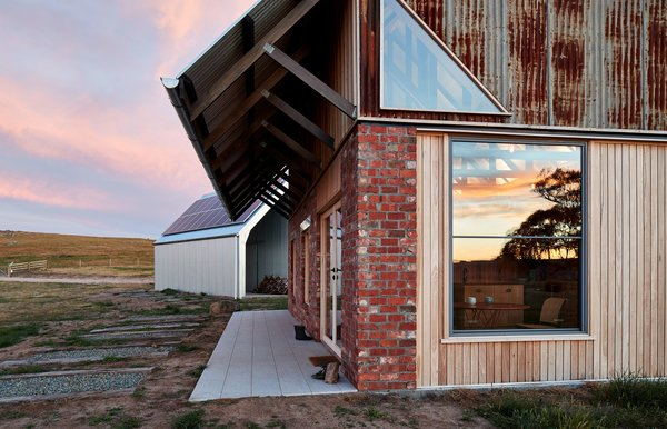 """The exterior combines recycled brick, radial sawn timber, and galvanized roof sheeting. """"Materials were selected to meet the clients' brief that the house fit within the cognitive idea of an old shed,"""" explain the architects."""
