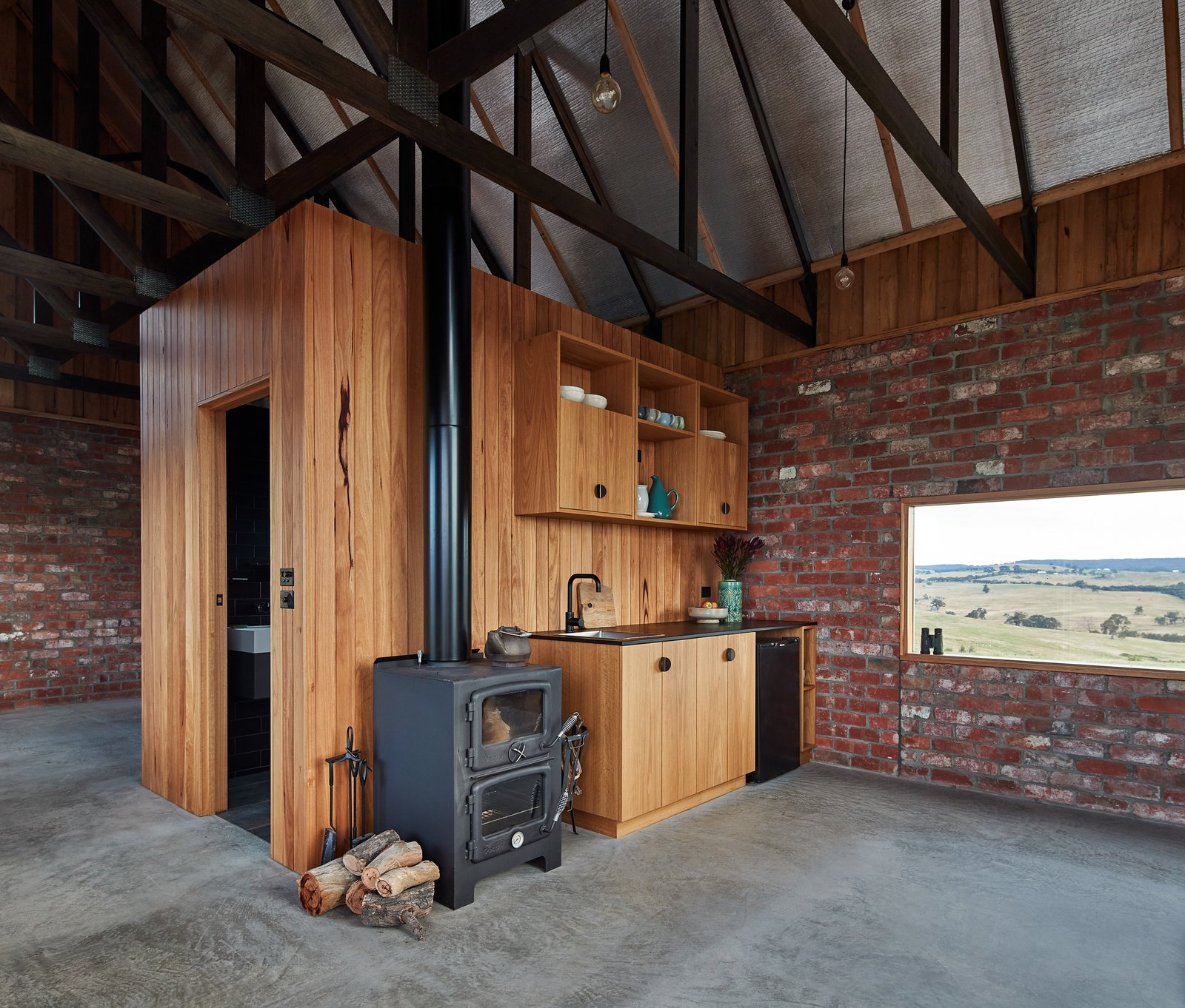Kitchen, Drop In, Refrigerator, Ceiling, Pendant, Wood, Concrete, and Wood A central core houses the bathroom and divides the bedroom from the kitchen/living area.    Best Kitchen Concrete Refrigerator Wood Ceiling Drop In Wood Photos from Simplicity Reigns at This Off-Grid Australian Retreat
