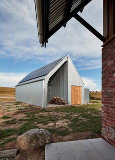 The shed was custom-designed with a shed kit company, and is clad in heritage-grade corrugated galvanized iron. It houses land-care equipment, as well as the PV panels and battery.