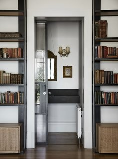 The architects repeated the use of glass and steel on internal openings as well, such as in the pocket door for this hidden nook, so as to produce visual consistency throughout the home.