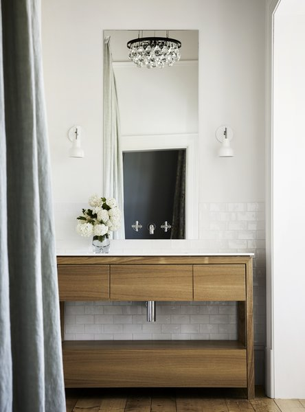 In a bathroom, the original wood floors sync nicely with a bespoke wood vanity, while glossy subway tile lends an aged quality that contrasts with the frameless mirror and modern, glass-mounted faucet.
