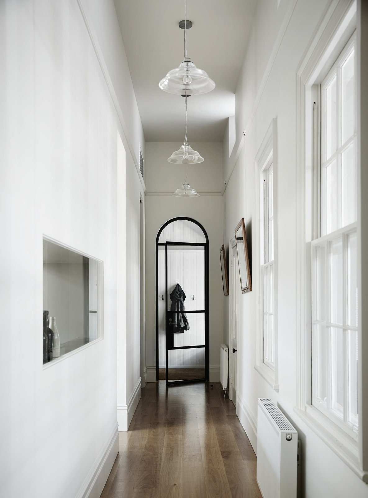 Hallway and Medium Hardwood This view shows how the steel-framed glass was elegantly melded with historic architectural details like the arched hallway opening.  Best Hallway Medium Hardwood Photos from Light Floods This Dazzling Renovated Victorian in Australia