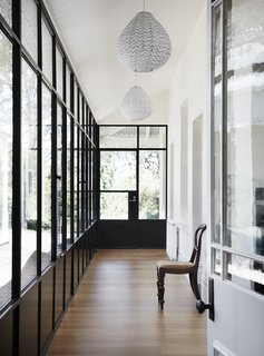The light-filled hallway created by enclosing a veranda with steel-framed glass.
