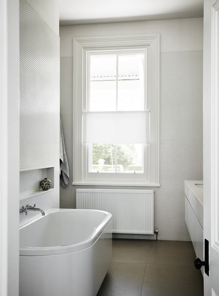 In another bathroom, white penny rounds cover the walls. The original window and casework give off historic gravitas and provide a thoughtful counterpoint to the modern tile treatment.