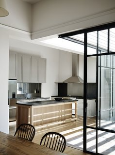 The revamped kitchen is now surrounded by retractable walls of glass. The architects carefully balanced old and new in all of the finishes, here combining classic Shaker cabinet fronts with a more streamlined, modern island.