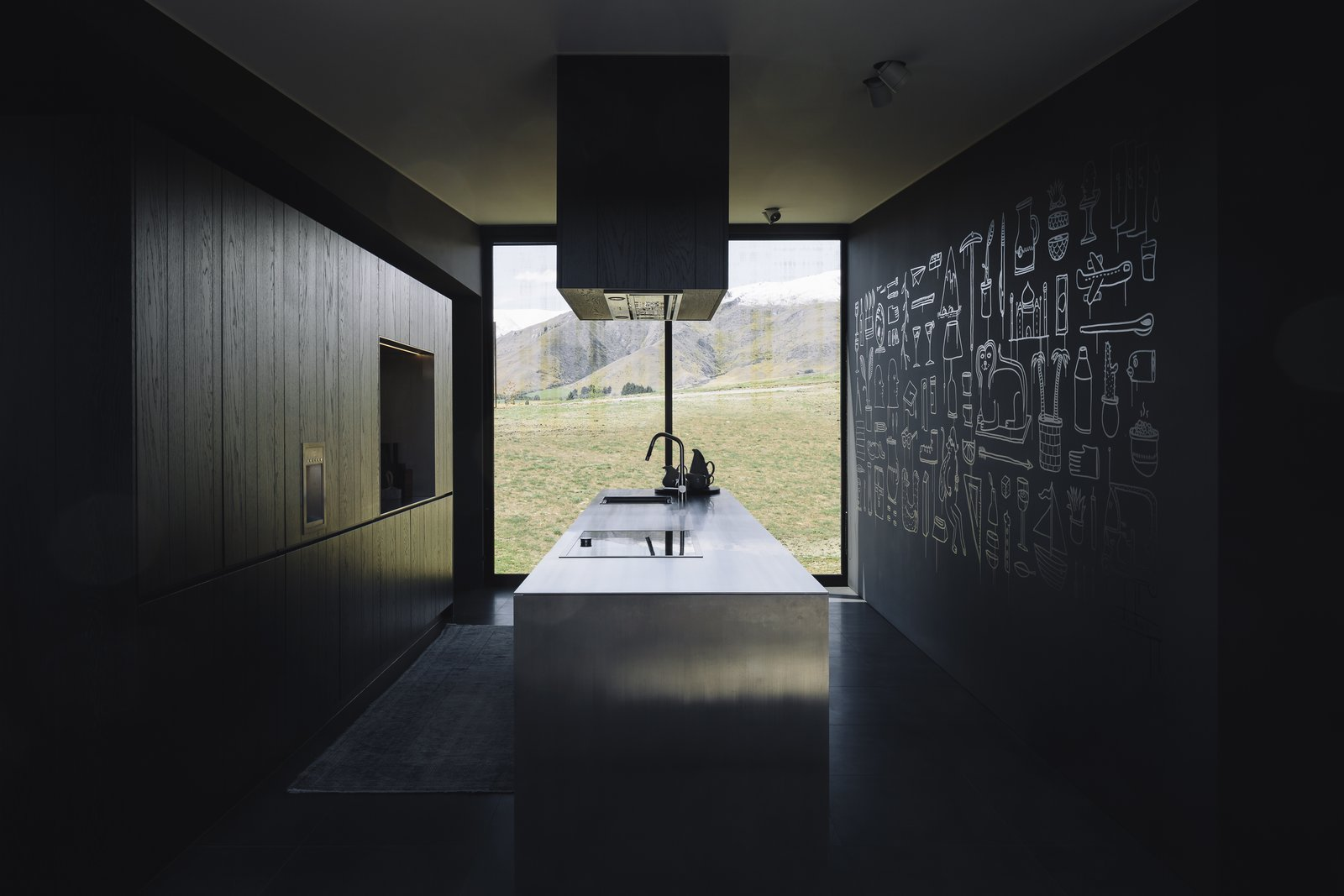Kitchen, Range Hood, Wall Oven, Cooktops, Undermount, Refrigerator, Wood, Ceiling, Ceramic Tile, and Wood Floor to ceiling glass frames the view in the kitchen.  Kitchen Cooktops Undermount Ceramic Tile Photos from A Striking Black House Appears to Float in the New Zealand Mountains