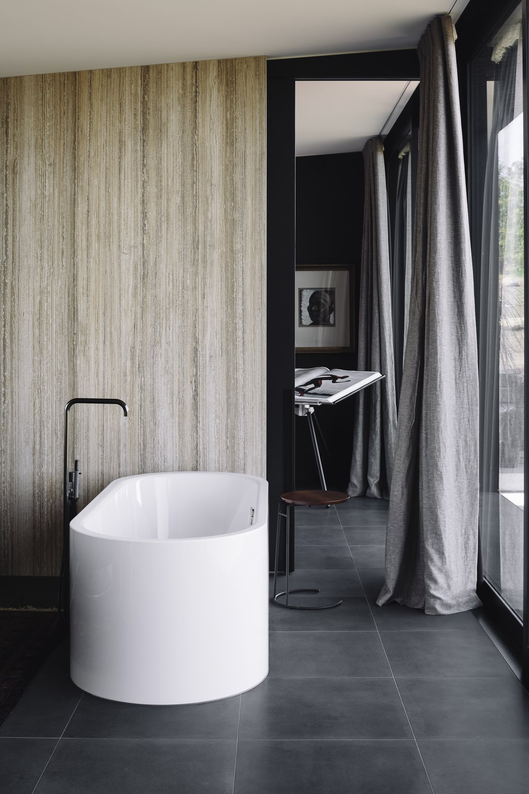 Bath, Stone Slab, Freestanding, and Ceramic Tile A travertine-clad bathroom interior was inspired by spa retreats much-loved by the owners.  Best Bath Freestanding Ceramic Tile Photos from A Striking Black House Appears to Float in the New Zealand Mountains