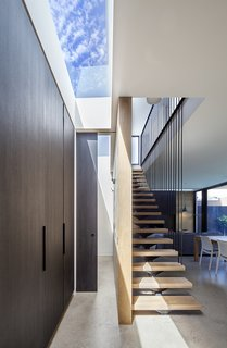 "A staircase with floating oak stair treads and a continuous steel railing goes up to the second floor. The cupboards on the left are fronted with the same ""Ravenswood"" panels, and a skylight floods the space with light."