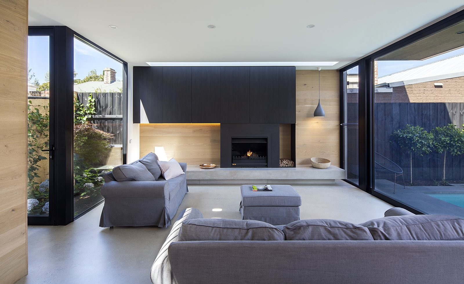 Living Room, Wood Burning Fireplace, Concrete Floor, Sofa, Ottomans, Recessed Lighting, Standard Layout Fireplace, and Pendant Lighting A modest polished concrete slab floor with hydronic in-slab heating anchors the new, open-concept living spaces.  Photo 2 of 11 in A Streamlined Addition Serves a Family of Four in Australia