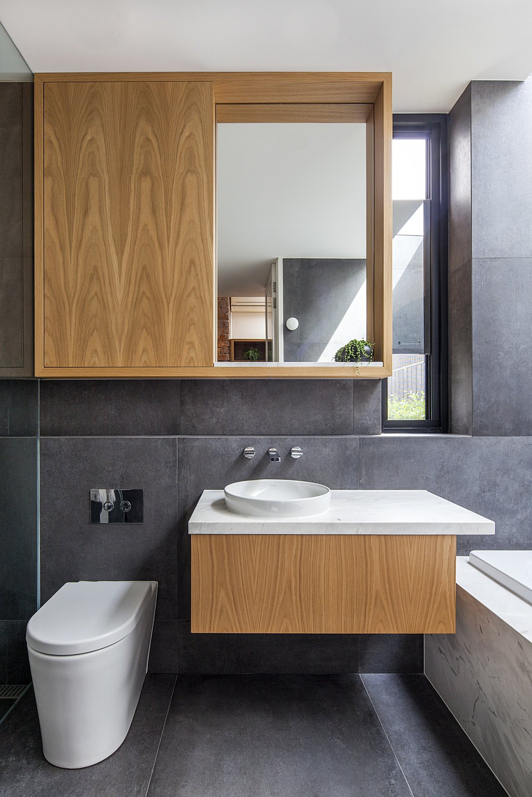 Bath Room, One Piece Toilet, Drop In Tub, Vessel Sink, and Marble Counter Oak cabinetry topped with marble continues the kitchen's themes in a bathroom.  Photo 9 of 11 in A Streamlined Addition Serves a Family of Four in Australia