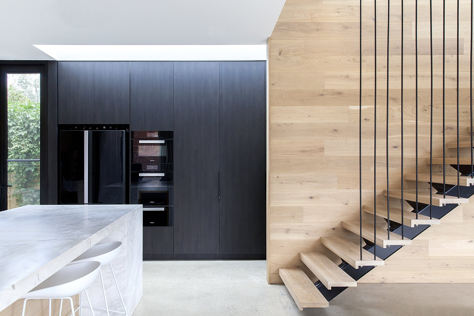 "Kitchen, Concrete, Refrigerator, Marble, Wall Oven, Microwave, and Wood A bank of pantry cabinets are clad in the ""Ravenswood"" panels to disguise sleek, black appliances.  Best Kitchen Concrete Refrigerator Microwave Photos from A Streamlined Addition Serves a Family of Four in Australia"