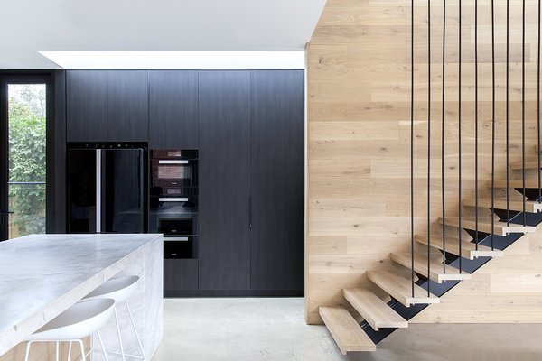 "A bank of pantry cabinets are clad in the ""Ravenswood"" panels to disguise sleek, black appliances."
