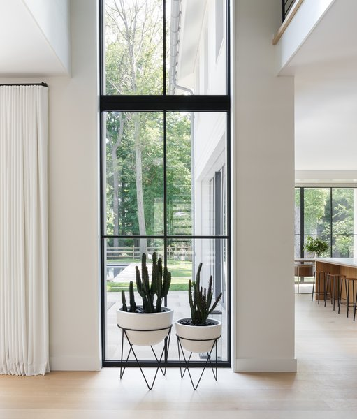 A two-story window floods the inside with light. The planters are from West Elm.