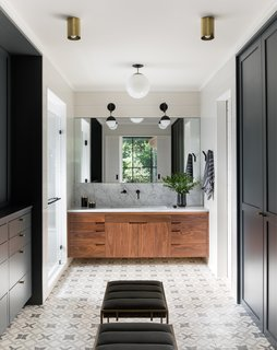 In the master bathroom, the Clé Tile floor, custom walnut vanity, and marble counter fashion a luxe retreat. Lighting is from a mix of manufacturers, including One Forty Three, Rejuvenation, Cedar & Moss, and Atelier de Troupe. The faucet is from Watermark.