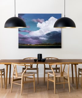 In the dining room, a table custom-made in Denmark by KBH is surrounded by Wishbone Chairs. The oversized pendants are from Luminaire Authentik.