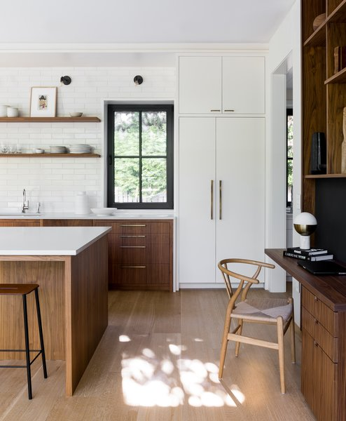 A modern desk was incorporated into the built-in walnut unit that separates the kitchen from the dining room, and has been accented with a Hans J. Wegner Wishbone Chair. The refrigerator and freezer columns are Thermador and the wall sconces are by Cedar & Moss.