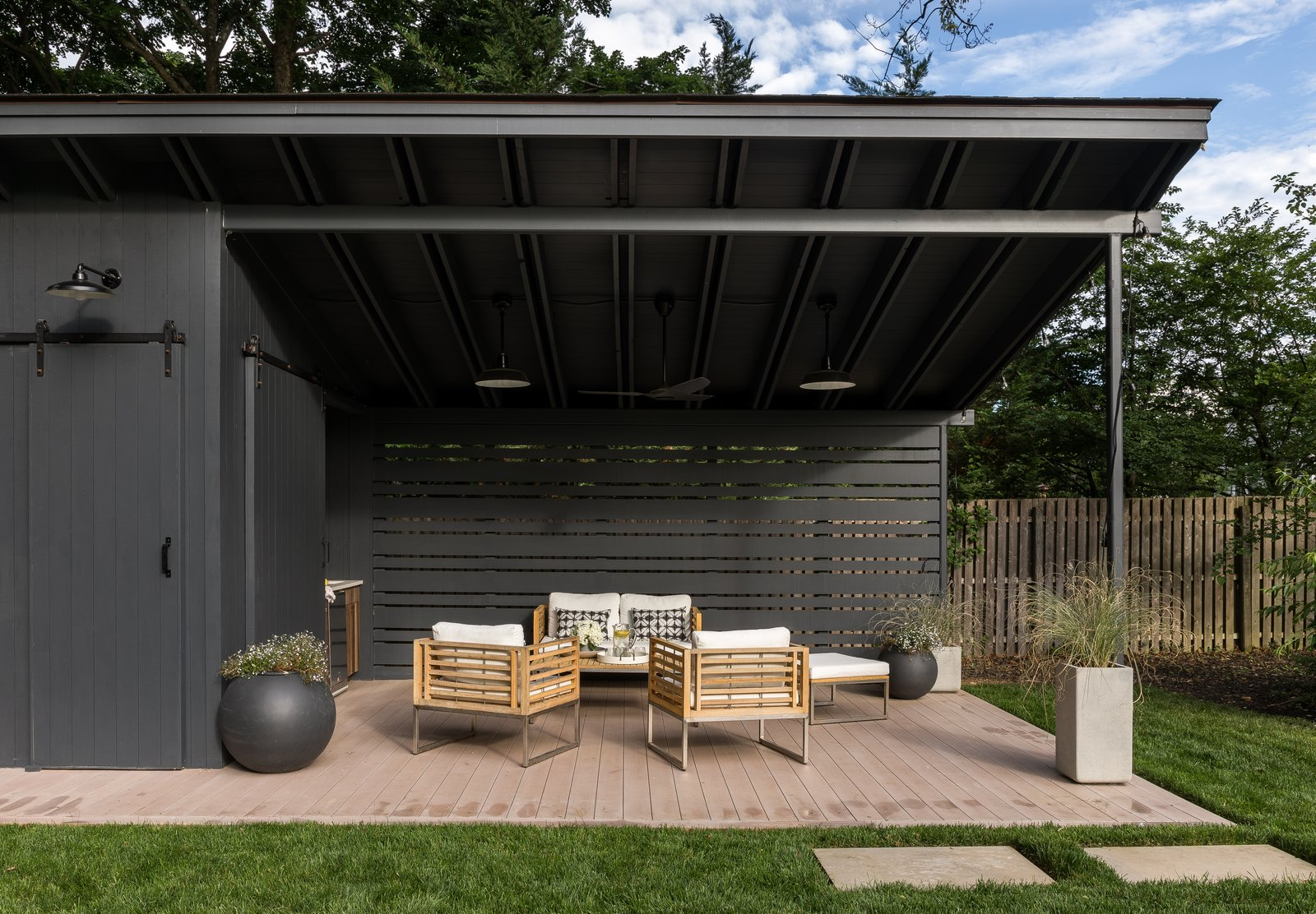 Outdoor, Large, Hanging, Back Yard, Hardscapes, Trees, Wood, Grass, Wood, Pavers, and Vertical The second seating area features furniture from All Modern.  Best Outdoor Pavers Wood Photos from A New Jersey Neighborhood Gets a Gorgeous Passive House