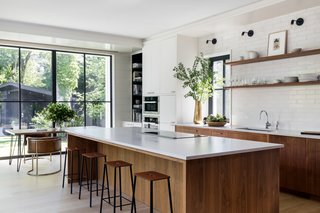 "In the kitchen, White Oak floors, inset walnut cabinets, Fireclay subway tile, and Caesartone countertops read more classic vibes, while the furnishings—such as the Reno Table from Structube, Channel Chairs by Industry West, and ADAM Stools by Frama Denmark—are modern counterpoints. Appliances include a Thermador 36"" Freedom Induction Cooktop and an inconspicuous Thermador 36"" Downdraft Ventilation, as well as a Miele Dishwasher, convection oven, and speed oven."