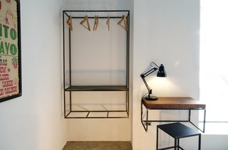 A sleek wall-mounted closet and a small desk, both fashioned from steel and wood, save space in a smaller room.