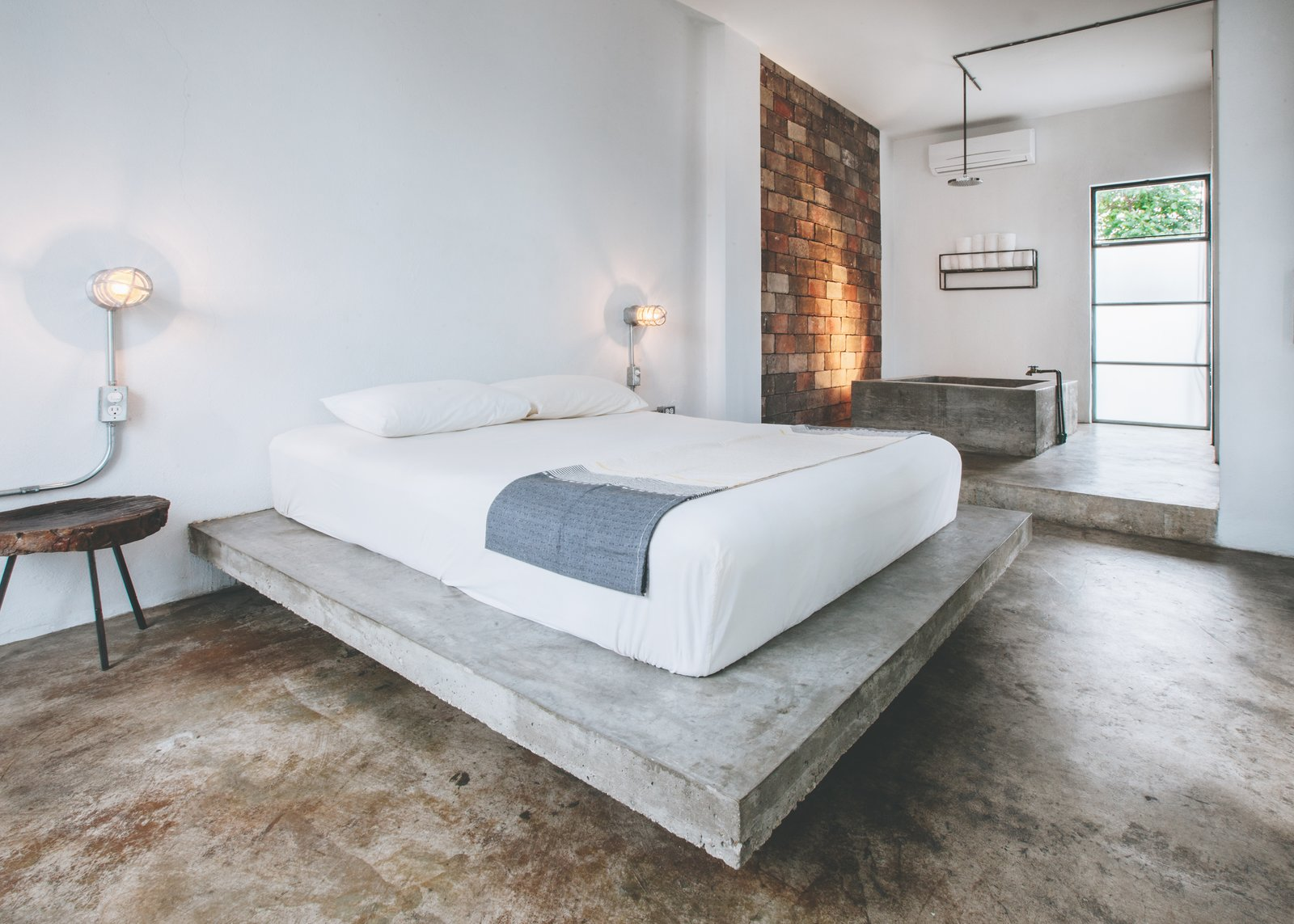 Bedroom, Bed, Accent, Wall, Night Stands, Lamps, and Concrete A 270-square-foot guest room includes a poured concrete tub with a rainhead shower.   Best Bedroom Bed Concrete Wall Night Stands Photos from Become a Hotelier in a Surfer's Paradise With This Chic Boutique Property Asking $2.6M