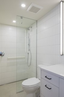 The bathroom is sheathed in Dal Tile, with a Silestone countertop placed over an IKEA cabinet. The curb-less shower supports aging in place.