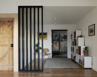 A simple partial screen separates a small sitting area with a door leading outside.