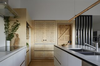 Inset perforated doors conceal a deep appliance garage and pantry to better hide cereal boxes and toaster. When opened, the doors slide back into pockets on either side of the cabinet.