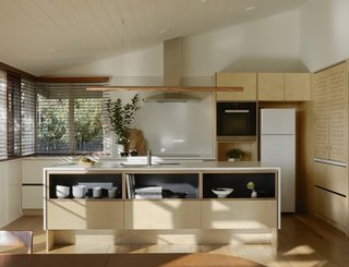 Birch plywood cabinetry outfits a streamlined kitchen space. The raw copper pendant over the island is from Giffin Design.