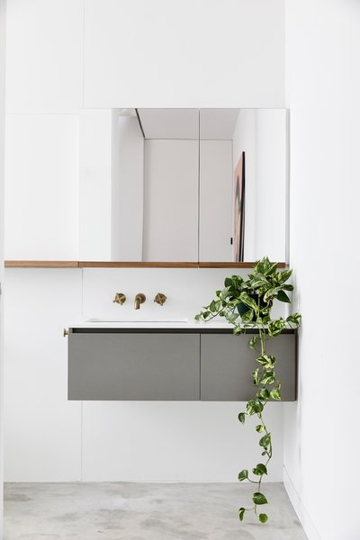 Bathroom finishes are an inversion of the darker palette in the main spaces, using a white reconstituted stone counter atop a laminate cabinet, with blackbutt shelves and brass faucets.