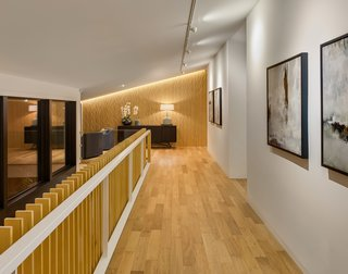 """To create a subtle interior rhythm, the upper level hallway has a feature wall with the same """"waving wood"""" pattern as the front door."""