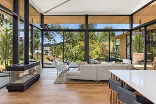 """Interior spaces, such as the main living area, deliberately frame exterior views. Per the architects: """"Thus, the beautiful oak trees on the opposite side of the creek are still 'belonging' to this house by the use of a technique called shakkei or borrowed scenery—to expand limits visually."""""""