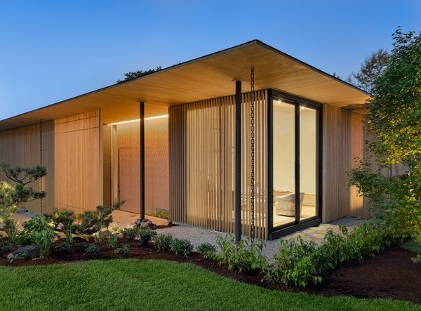 """The entry is tucked behind a louvered screen, creating a winding path to the front door. The screen, composed of Alaskan Yellow Cedar, shields views from the sidewalk while still allowing interior occupants to see out, and evokes """"a sense of elegance, mystery, and warmth,"""" says the firm."""