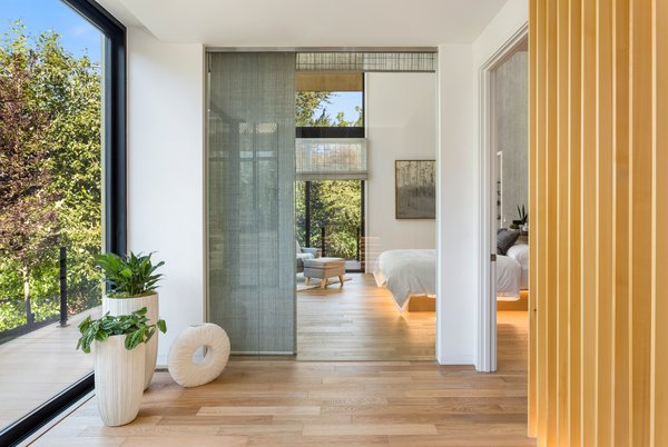 The main floor master bedroom also enjoys the views via the double-height glass.
