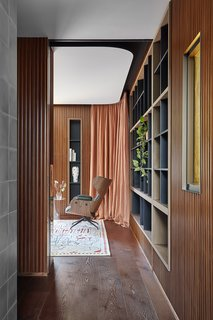 A curved ceiling gently hovers over the stricter lines of the wall paneling and inset shelves.
