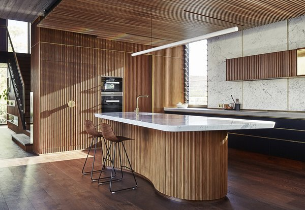 "The shape of the kitchen island ""reflects the local iconic beachside concrete kiosk building saved by the community,"" said the architects."