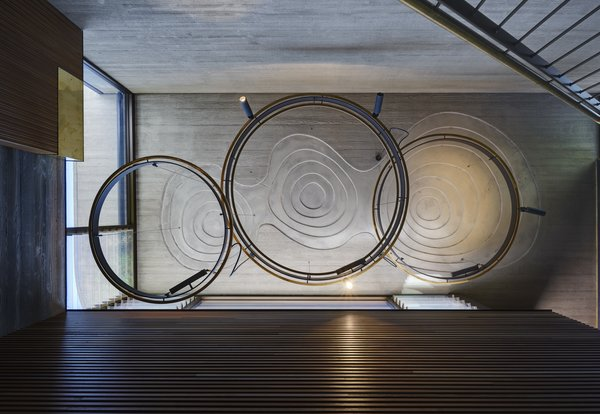 The custom-designed pendant lights over the stairs echo the undulating recesses in the concrete ceiling. That sinuous motif is repeated in various ways throughout the project.
