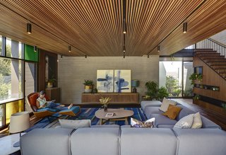 In the living room, the wood and concrete shell is accented with a steel stair railing and a window wall with a Mondrian pattern in the glazing.