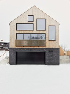 The natural slope of the site was perfect for dividing the house into split levels. The exterior is clad in heat-treated pine that has aged to a soft gray, which contrasts nicely with the charcoal bricks.