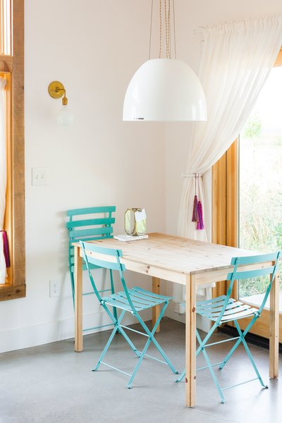 A petite dining table is surrounded by sky blue chairs that sync with the nearby kitchen cabinets. The pendant is the Factory Light No. 9 Pendant from Schoolhouse Electric.