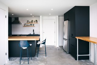 Now, the kitchen's workspace has been considerably expanded, which makes it multi-functional. During the day, it's Kevin's design studio; at night, it's ready for relaxing. Black IKEA cabinetry is a streamlined backdrop for the warm wood accents and geometric wall tile, the latter from Wayfair. The stools are from Blu Dot.