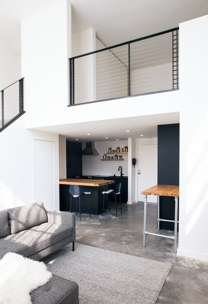 Now, crisp white walls and the refinished concrete floor conjure the loft's urban roots. Sleek black kitchen cabinets sync up nicely with the new metal railing.