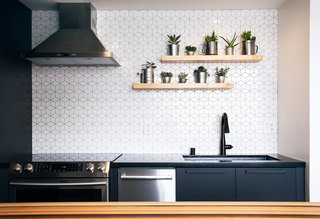 The kitchen backsplash features geometric wall tiles from Wayfair, while floating, open shelves create a pleasing display of mini succulents.