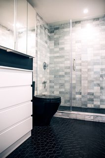 In the new bathroom, the couple chose black floor tile from Wayfair, selecting a shape similar to the kitchen tile for consistency. The marble shower tile was a Home Depot find, as was the Toto toilet.