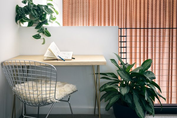 When it comes to home office design, IKEA is a great place to look for functional pieces like desks and lamps. Find items similar to this simple yet modern, handmade desk that rests in an alcove the homeowners have made into a small home office.