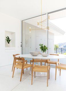 Farnham squared off the ill-fitting addition and specified large-scale, sliding glass doors from Fleetwood that match the rest of the home and let the breakfast nook open to the exterior. A white Saarinen-style table is surrounded by wooden chairs with woven seats, which were intended to warm the scheme.
