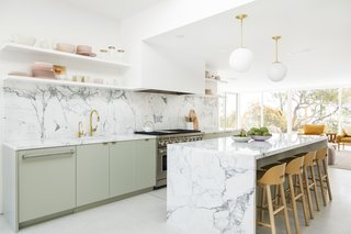 "Thick Calacatta marble counters wrap streamlined sage green flat-front cabinetry, painted in Farrow & Ball's ""Mizzle."" The island pendants are Cedar & Moss, and the Alfi Low-Back counter stools are by Jasper Morrison for Emeco."