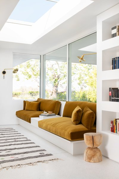 A custom built-in sofa upholstered in whiskey-colored velvet from Fabricut now makes for the perfect reading spot. The swing arm sconces are from Photonic Studio.
